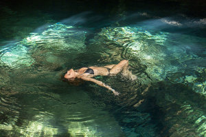 Woman floating in water in a relaxed pose in a pool situated in a cenote.Getty Images #150086968