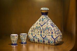 botella de tequila en cerámica con dos vasos tequileros