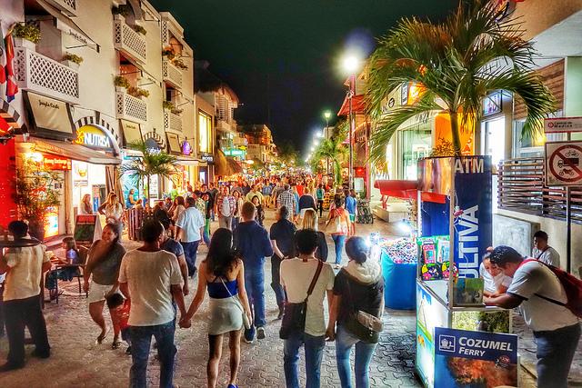 personas caminando en la quinta avenida en playa del carmen de noche