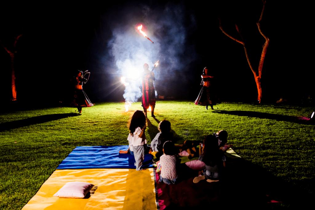infantes viendo un show de fuego acostados en el jardin de Grand Velas Riviera Maya